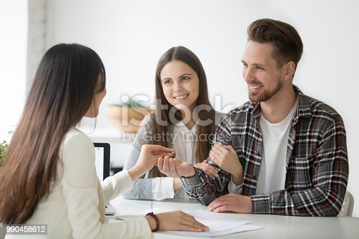 istock Smiling couple receiving keys to first apartment together 990458612