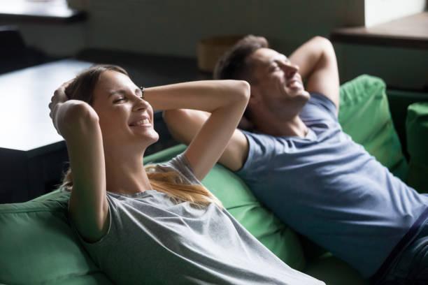 Couple souriant reposant sur la prise confortable canapé en pause pour se détendre - Photo