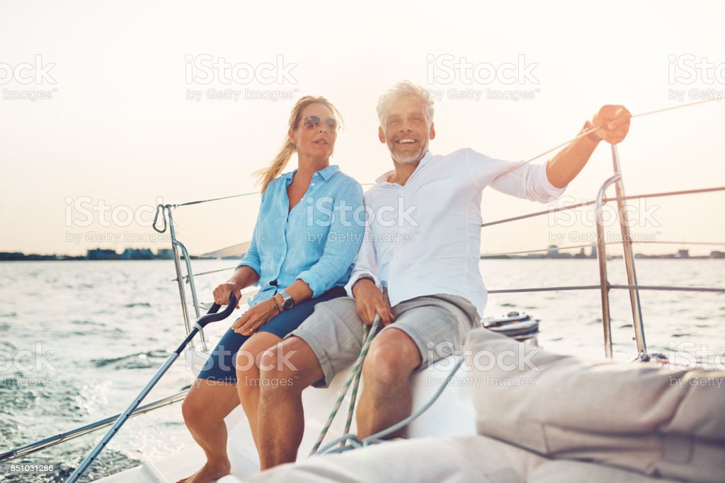 Smiling couple sailing their boat together on a sunny afternoon stock photo