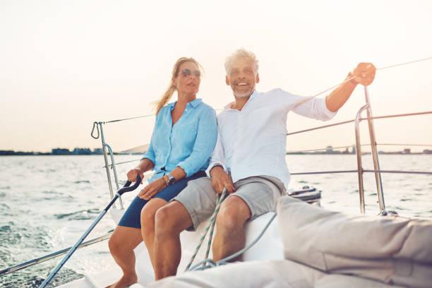 微笑對夫婦在一個晴朗的下午一起航行他們的船圖像檔
