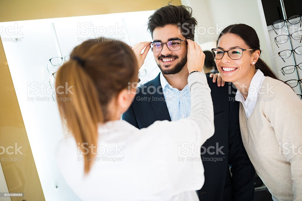 Smiling couple selecting eyeglasses in optical store stock photo