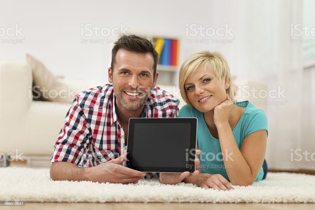 Smiling couple showing screen of digital tablet at home royalty-free stock photo