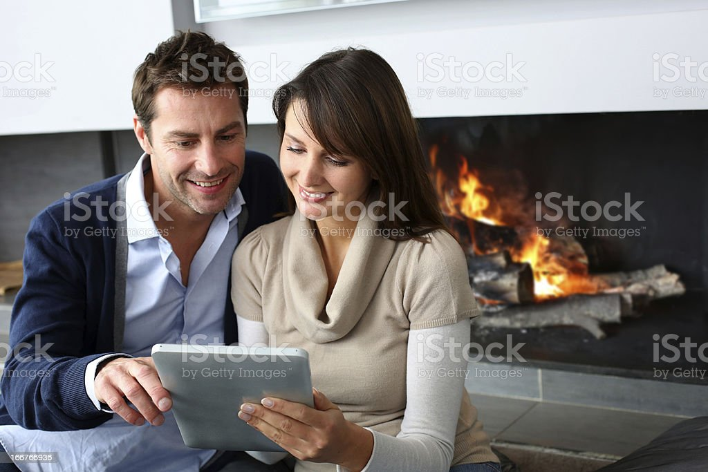 Smiling couple sitting by fireplace royalty-free stock photo