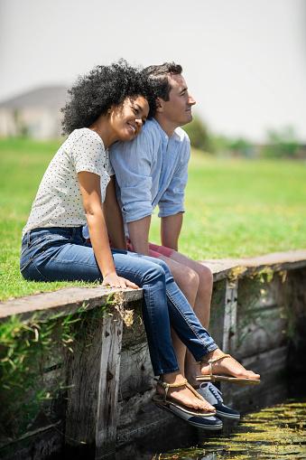 Smiling couple sitting by lake
