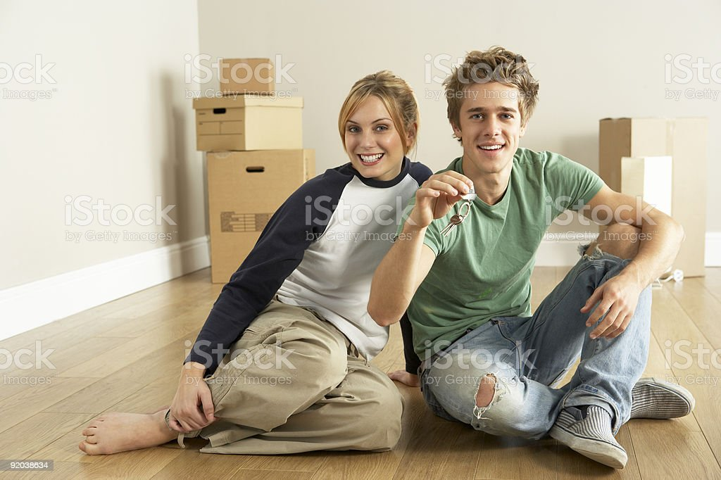Smiling couple sitting on new home's floors next to boxes royalty-free stock photo