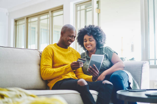 Smiling couple sitting on their living room sofa and using a tablet stock photo