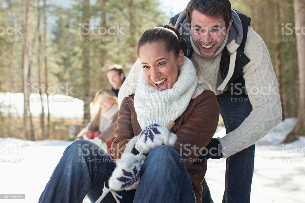 Smiling couple sledding in snowy woods royalty-free stock photo