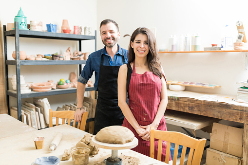 Smiling Couple Spending Time At Pottery Workshop
