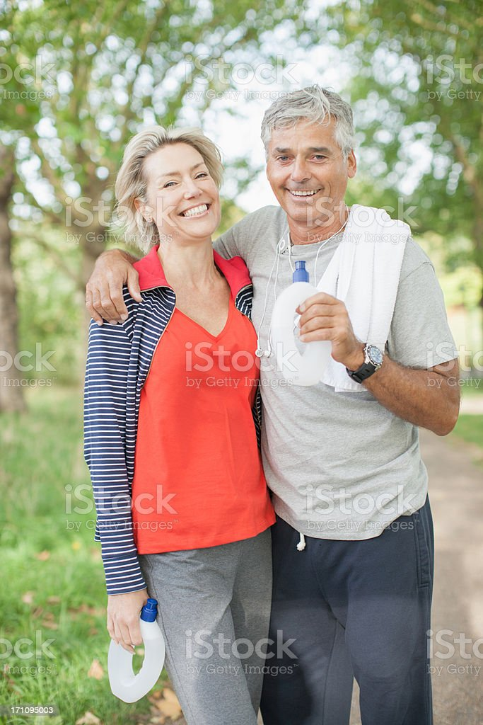 Smiling couple standing together with water bottle stock photo