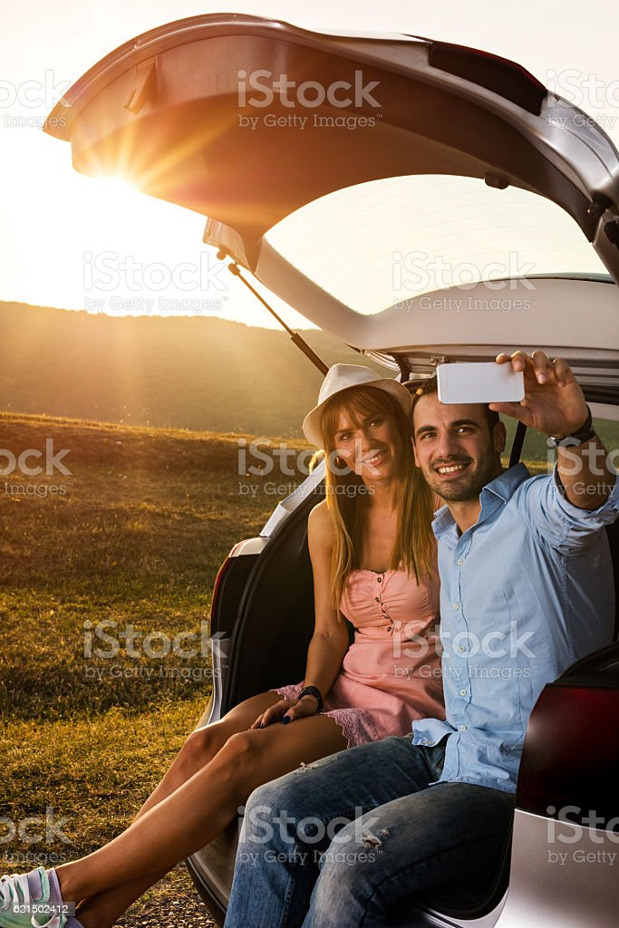 Smiling couple taking selfie with mobile phone on road trip. photo libre de droits