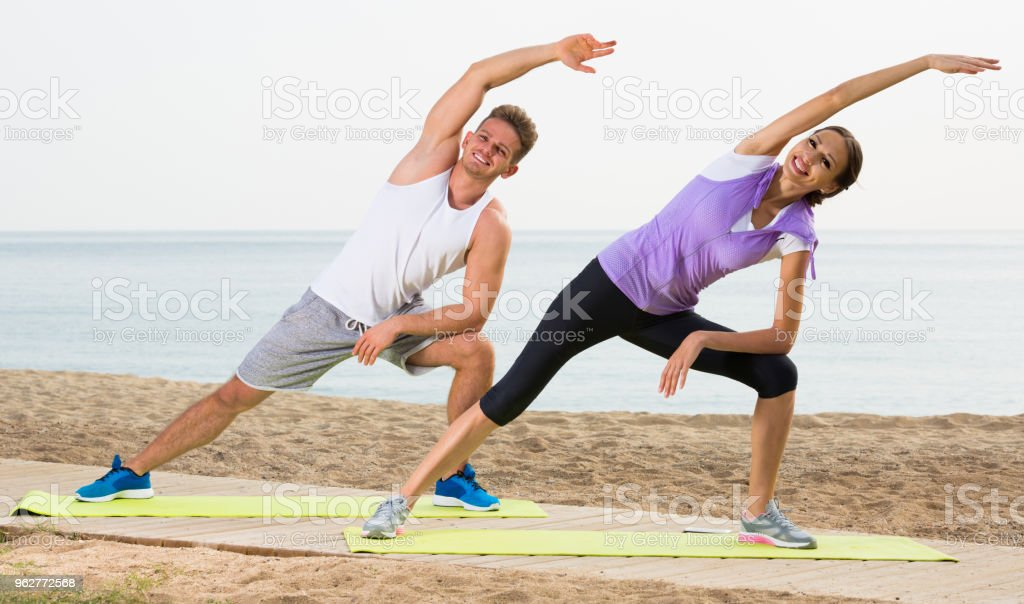 Smiling couple training yoga poses on beach - Foto stock royalty-free di 30-34 anni