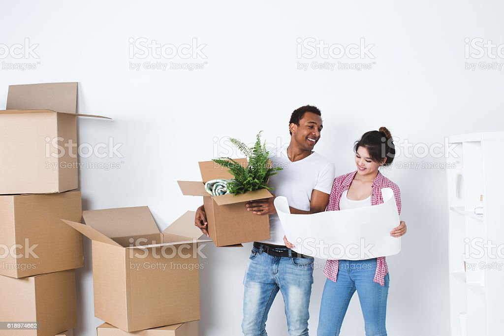 Smiling couple unpack boxes in new home. stock photo