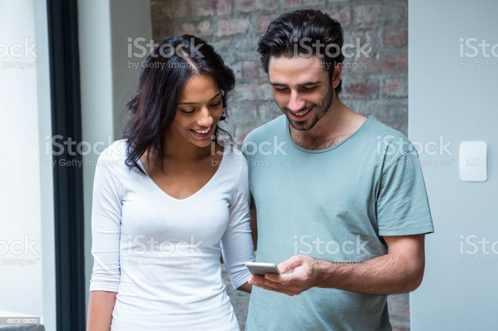 Smiling couple using smartphone together foto stock royalty-free