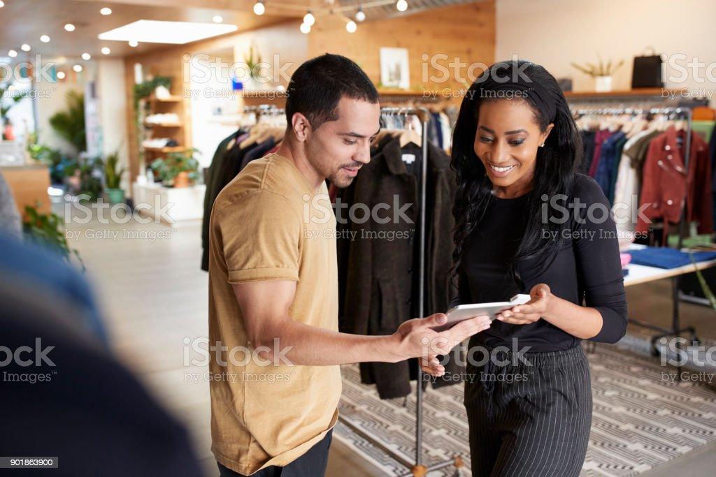 笑顔のカップルが洋服店でタブレット コンピューターを使用して ストックフォト