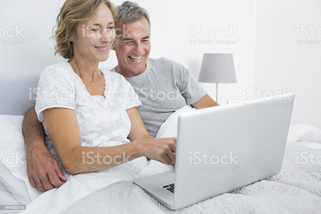 Smiling couple using their laptop together in bed stock photo