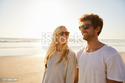 Smiling young couple talking together while walking along a sandy beach together on a sunny afternoon