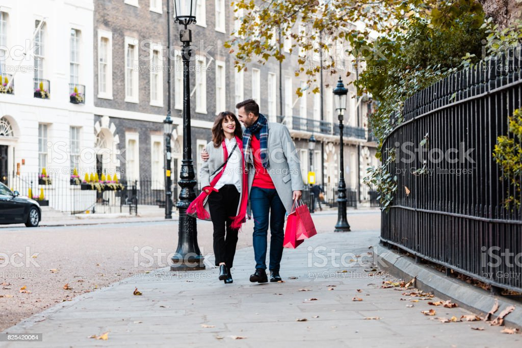 Smiling couple walking along the street with shopping bags stock photo