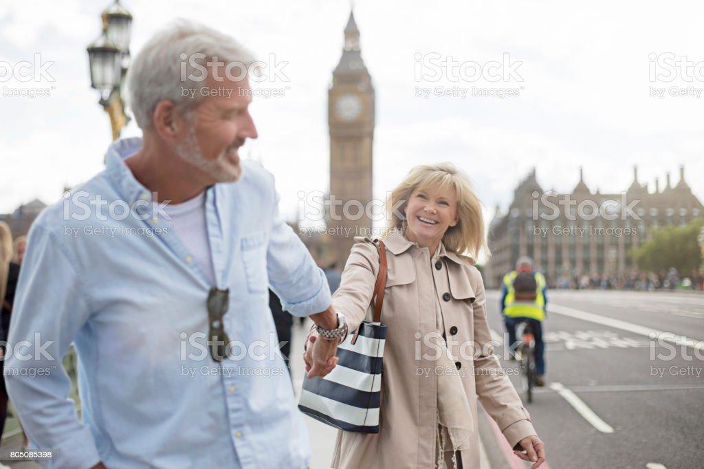 Smiling couple walking on Westminster Bridge stock photo