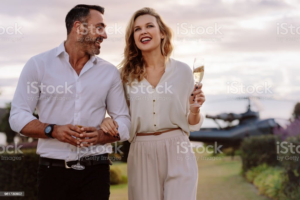 Smiling couple walking outdoors Smiling couple walking outdoors holding a glass of wine. Caucasian man and woman with a drinks walking together with a helicopter in background. Adult Stock Photo