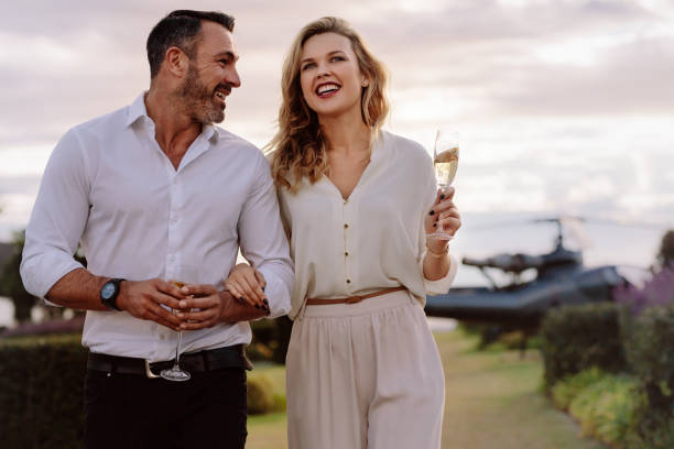 Smiling couple walking outdoors Smiling couple walking outdoors holding a glass of wine. Caucasian man and woman with a drinks walking together with a helicopter in background. grace stock pictures, royalty-free photos & images