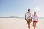 Smiling couple walking hand in hand together along a sandy beach during their summer vacation