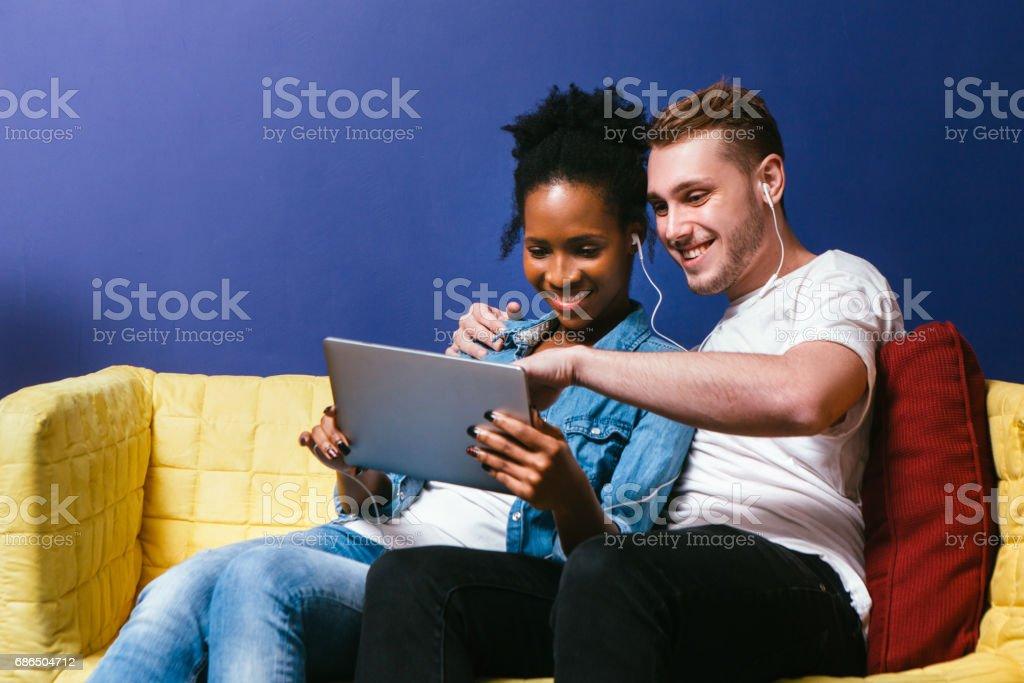 Smiling couple watch photos on tablet, sit at home royaltyfri bildbanksbilder