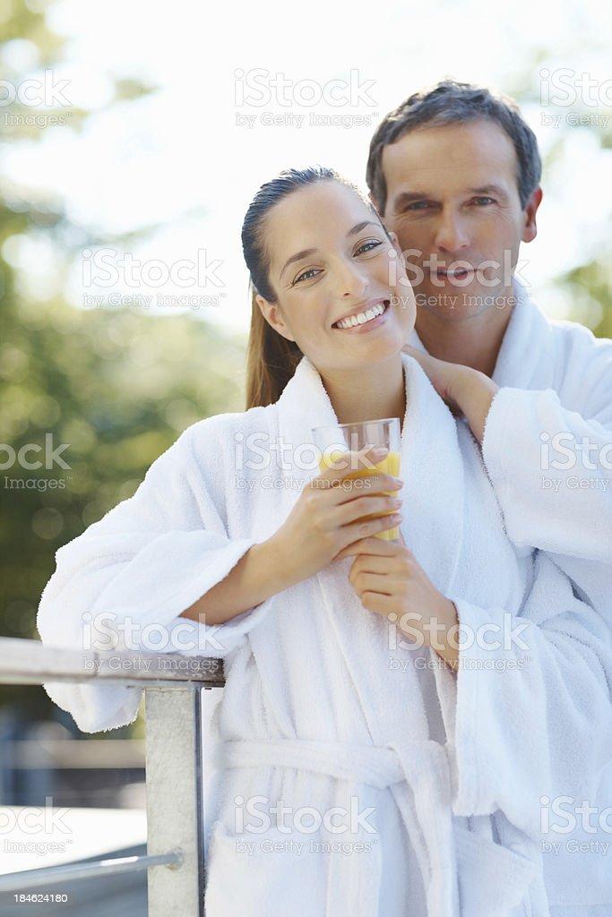 Smiling couple wearing bathrobes outdoors royalty-free stock photo