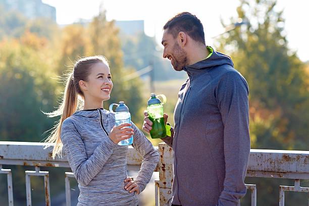 lächelnd paar mit flaschen wasser im freien - wasser trinken abnehmen stock-fotos und bilder