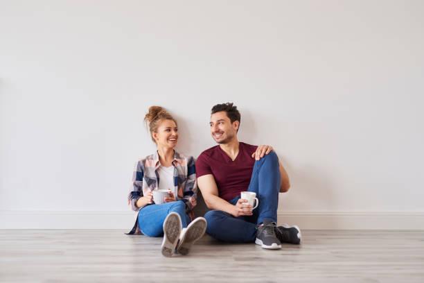 Lächelndes Paar mit Kaffee, der eine Pause vom Umzug nach Hause nimmt – Foto