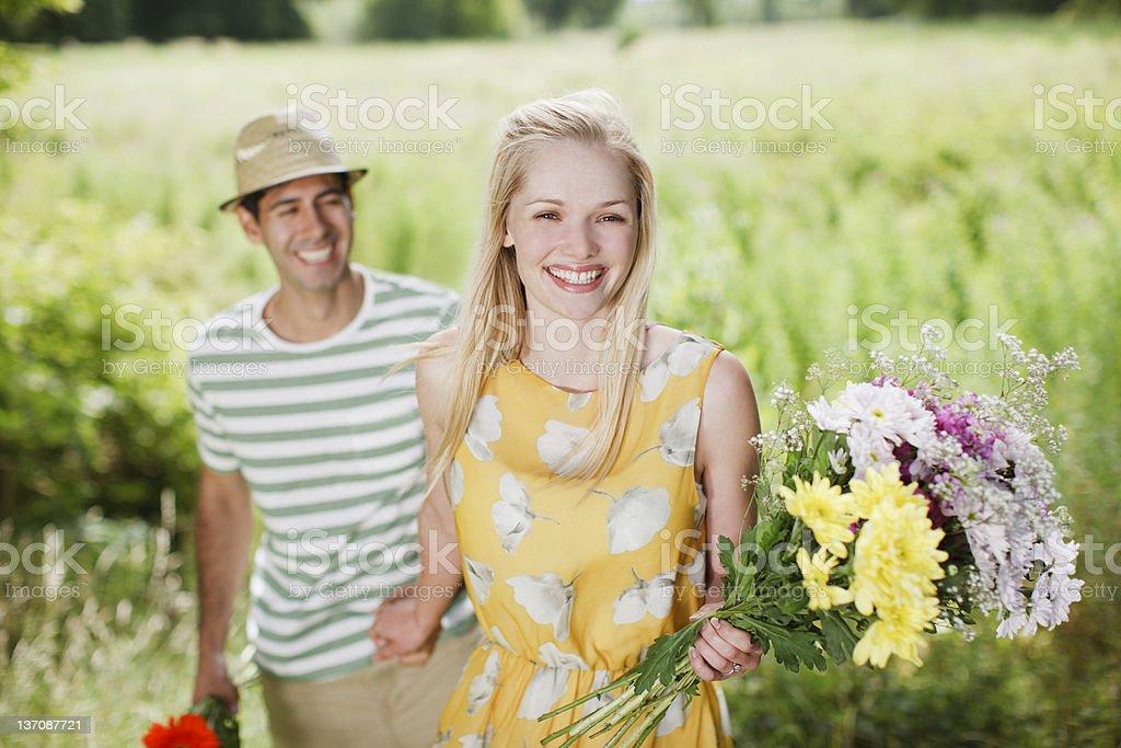 couple souriant avec fleurs dans la campagne du terrain - Photo