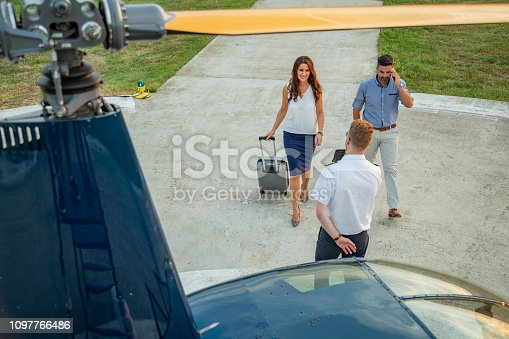 Smiling couple walking to pilot by helicopter, pulling luggage, using phone