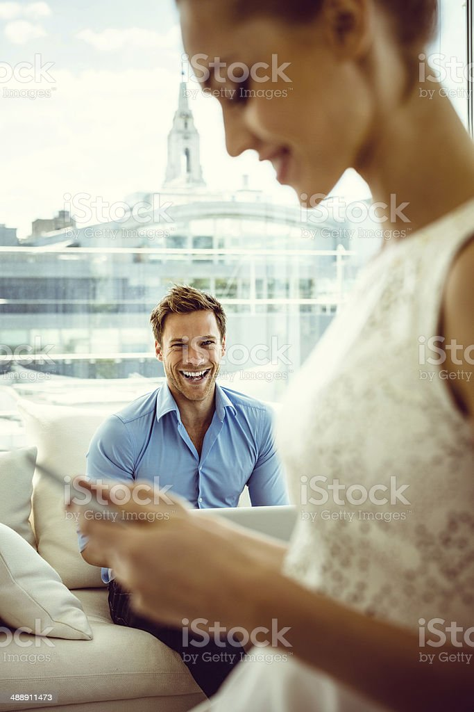 Smiling couple with technologies Focus on young man sitting on sofa in the apartment and using a laptop with the side view of a women texting on the foreground. 25-29 Years Stock Photo