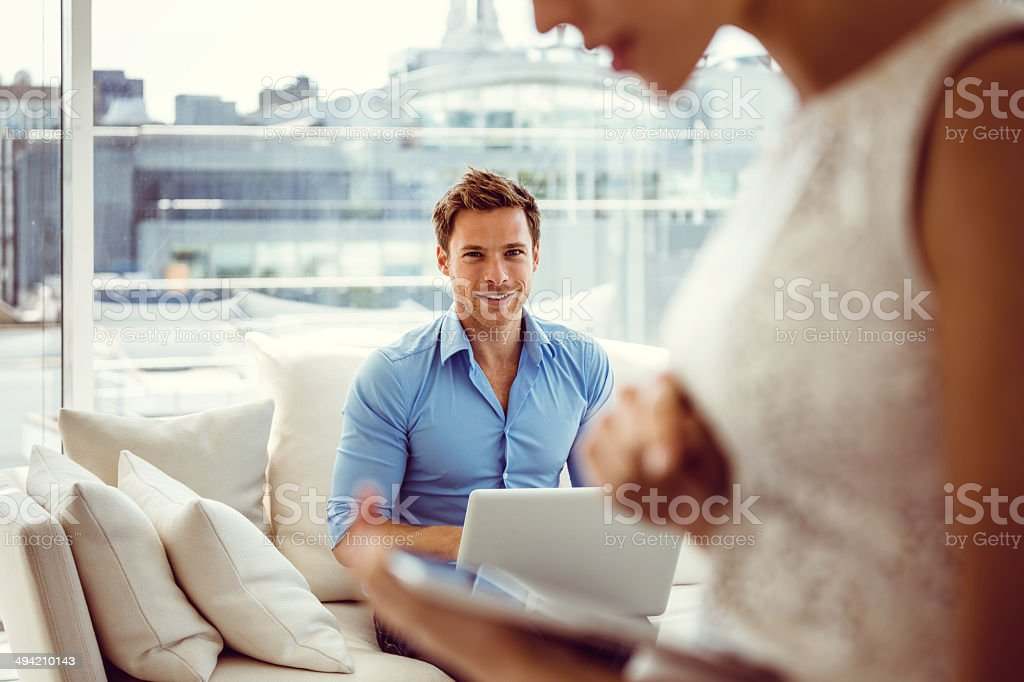 Smiling couple with technologies Focus on young man sitting on sofa in the apartment and using a laptop with the side view of a woman with the digital tablet  on the foreground. Elegance Stock Photo