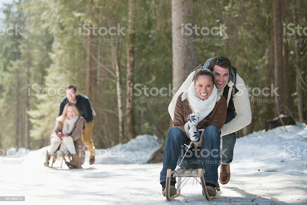 Smiling couples sledding in snowy woods royalty-free stock photo
