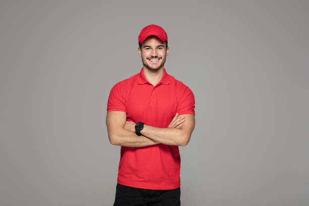 Smiling courier man posing in studio. Delivery Concept - Smiling Caucasian courier man posing on studio background. delivery man stock pictures, royalty-free photos & images
