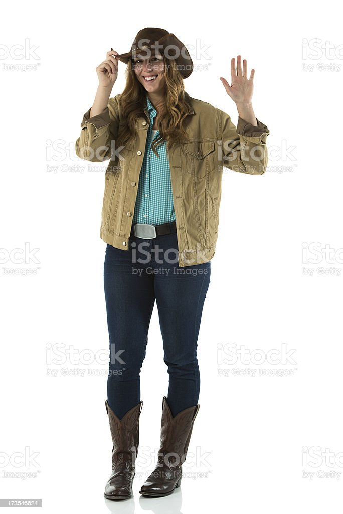 Smiling cowgirl gesturing against white royalty-free stock photo