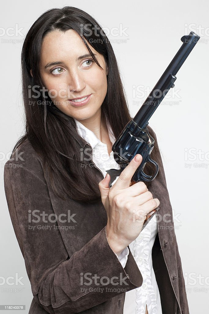 smiling cowgirl in suede shirt holds up big revolver (XXL) royalty-free stock photo