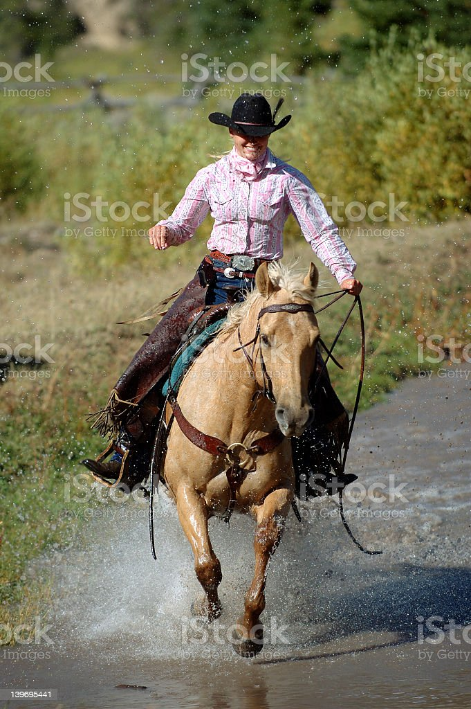 Smiling cowgirl on a horse crossing a pond stock photo