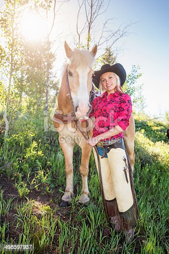 Cowgirl standing beside her horse on a green meadow in the sun. Montana, USA.