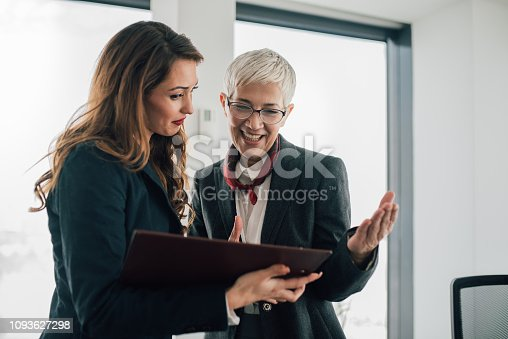 Happy business women looking at documents together