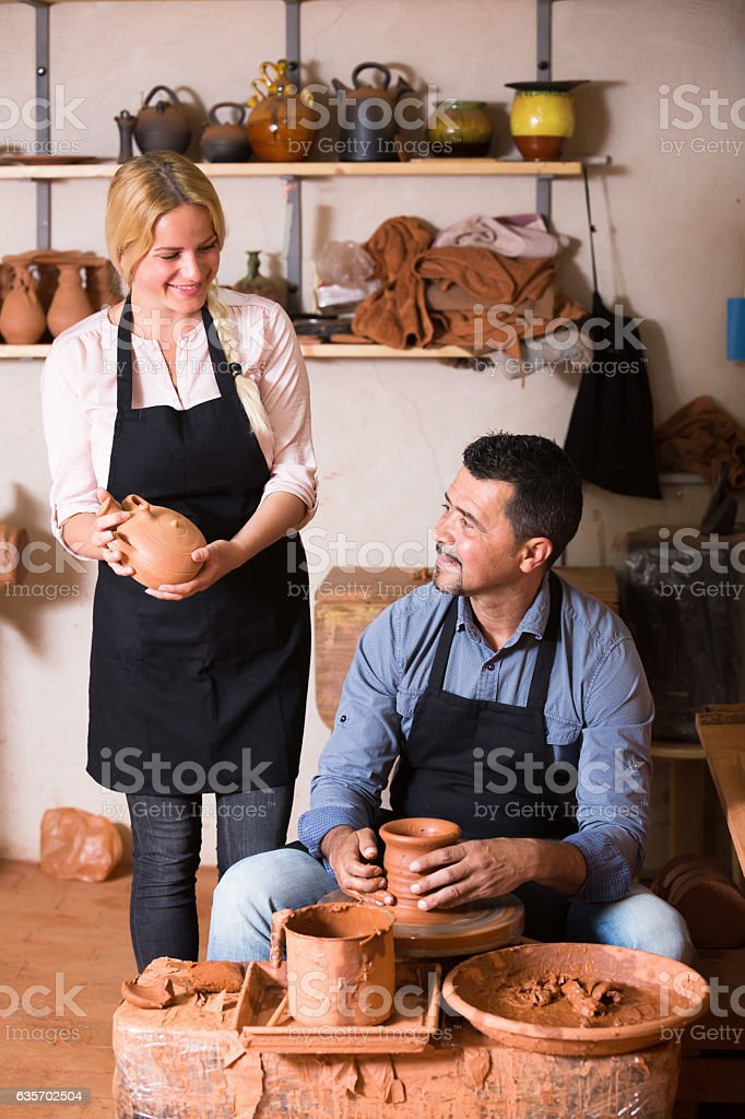 Smiling craftsman making pot using pottery wheel royalty-free stock photo
