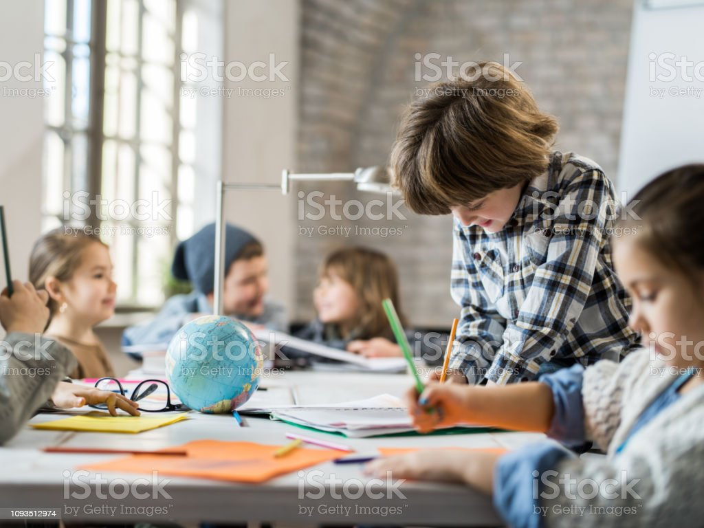 Cute creative boy writing while working with his friends in the...