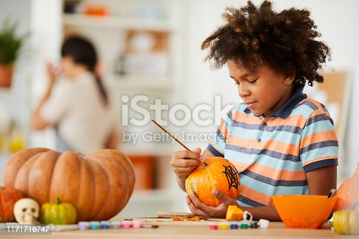 Smiling creative child with Afro hairstyle leaning on counter with gouaches and making design on pumpkin