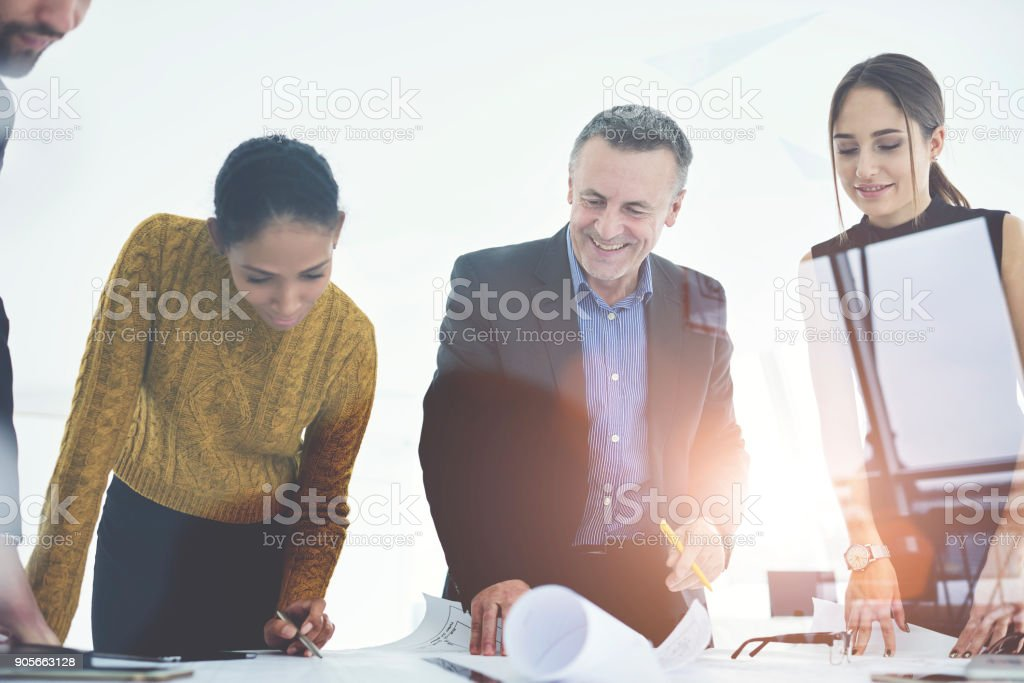 Smiling crew of architects satisfied with accomplished blueprint for project drafting together in office.Mature boss checking work of experienced engineers cooperating with employees in good mood stock photo