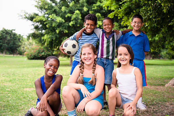 Smiling culturally-diverse group of children on soccer field stock photo