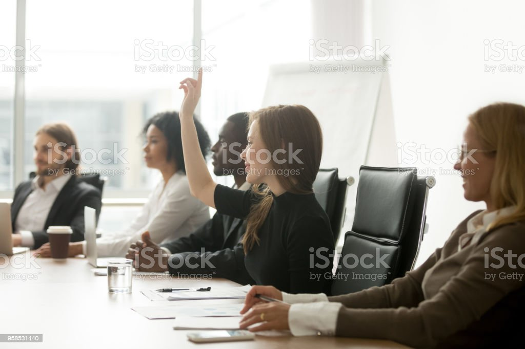 Smiling curious businesswoman raising hand at group meeting voting as volunteer stock photo