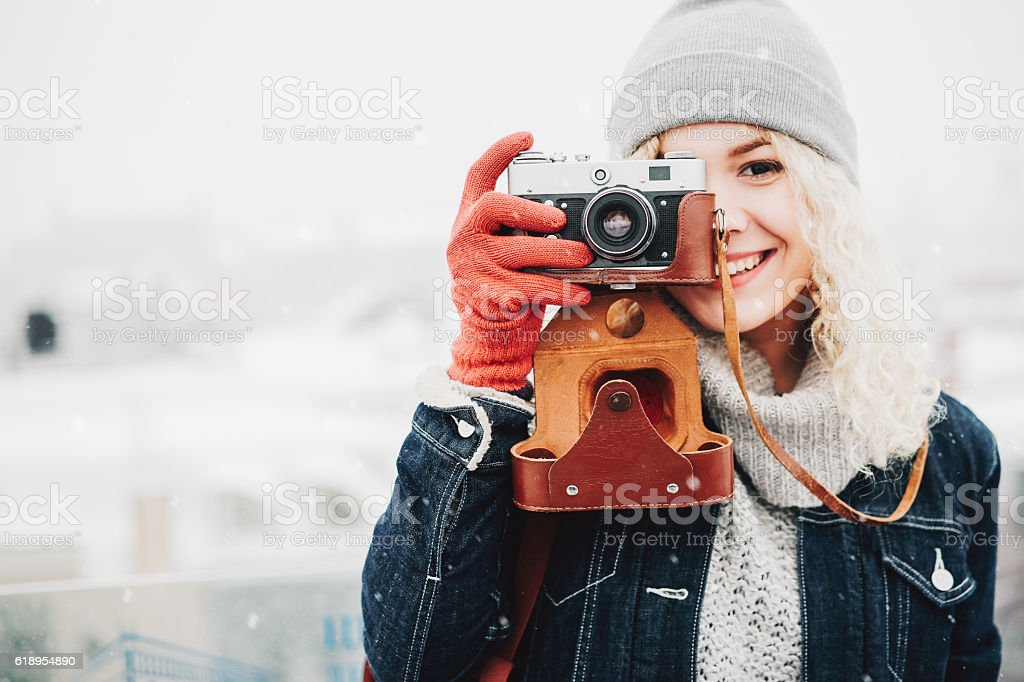Smiling curly blond girl with retro film camera stock photo