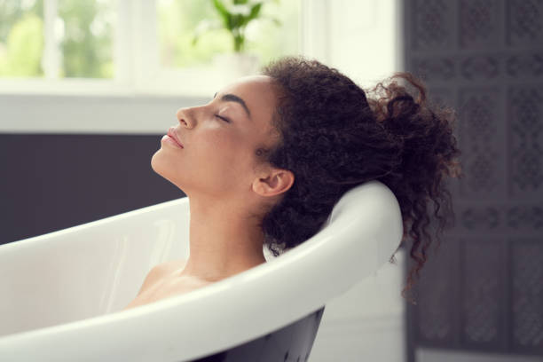 Smiling curly woman having rest in bathroom stock photo