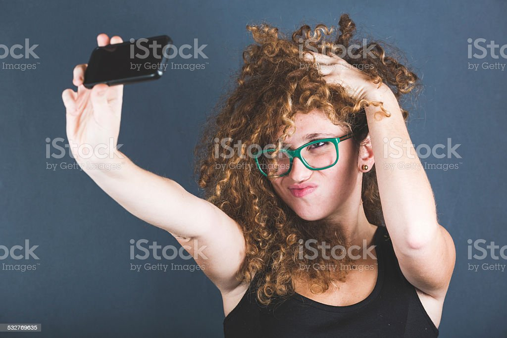 Smiling Curly Woman Taking Selfie stock photo