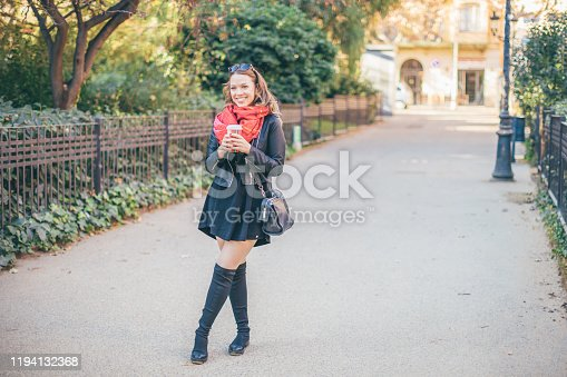 Smiling curvy blond hair woman standing on the street with cup of coffee to go
